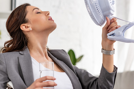 Beautiful businesswoman holding electric fan and glass of water with closed eyes while suffering from heat in office