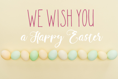 Top view of painted pastel chicken eggs on light yellow background with we wish you a happy Easter lettering Standard-Bild - 124382018
