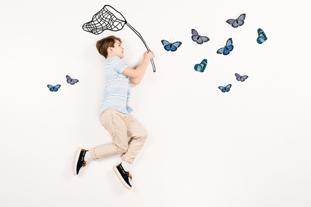 Top view of cheerful kid holding butterfly net near butterflies on white background