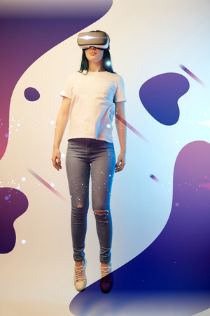 Young woman in virtual reality headset levitating in air among glowing and abstract purple illustration on beige background