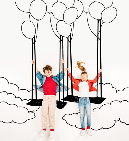 Top view of cheerful kids on swings near balloons and clouds on white background