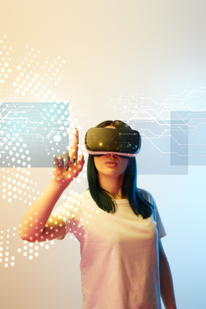 Young woman in virtual reality headset pointing with finger at network illustration on beige and blue background