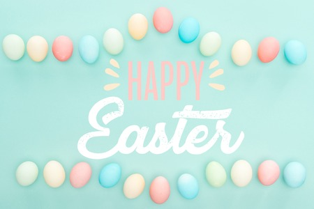 Top view of painted chicken eggs on blue background with happy Easter lettering Stockfoto