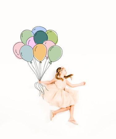 Top view of cute kid in pink dress holding colorful balloons on white background