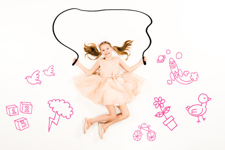 Top view of cheerful kid flying with jumping rope and smiling on white background