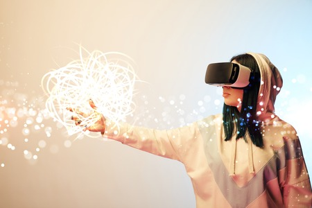 Young woman in virtual reality headset pointing with hand at glowing cyber illustration on beige and blue background