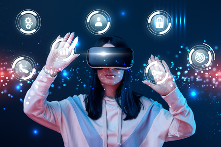 Young woman in virtual reality headset gesturing among glowing cyber icons on dark background Reklamní fotografie