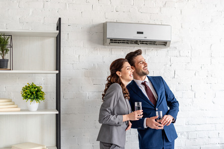 Smiling business people holding glasses of water while standing under air conditioner in office Foto de archivo