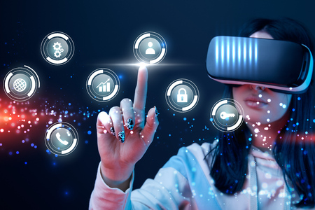 Selective focus of young woman in virtual reality headset pointing with finger at glowing cyber icons on dark background Standard-Bild