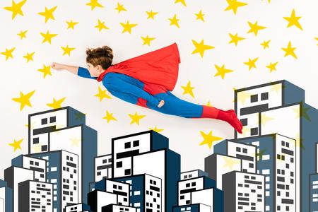 Vista superior del niño en traje de superhéroe volando cerca de estrellas y edificios sobre fondo blanco. Foto de archivo