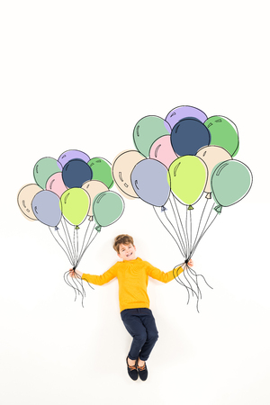 Top view of happy kid holding colorful balloons and smiling on white background