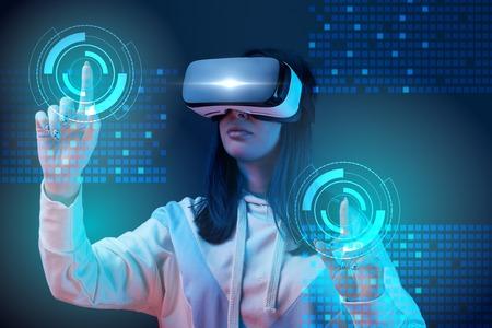 Junge Frau im VR-Headset zeigt mit den Fingern auf leuchtende Cyber-Illustration auf dunklem Hintergrund Standard-Bild