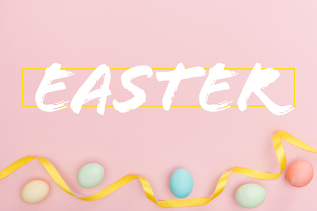 Top view of painted multicolored chicken eggs and satin ribbon on pink background with Easter lettering Banco de Imagens - 124382127