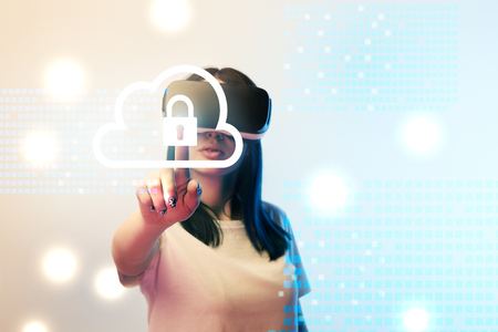 Young woman in virtual reality headset pointing with finger at internet security illustration on beige and blue background