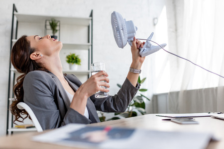 Selective focus of attractive businesswoman holding blowing electric fan and glass of water while suffering from heat in office