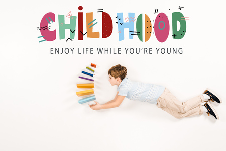 Top view of kid holding books and flying near childhood enjoy life while you're young lettering on white background
