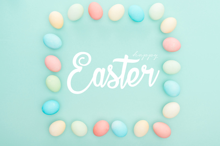 Top view of square frame made of painted chicken eggs on blue background with white happy Easter lettering