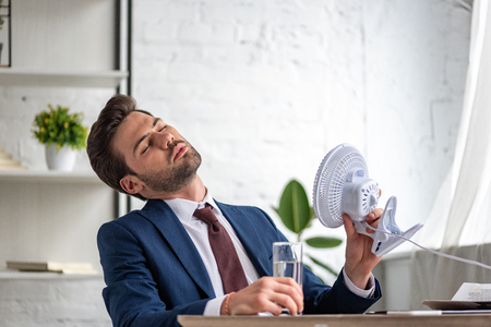 Young businessman holding electric fan while suffering from heat at workplace 스톡 콘텐츠
