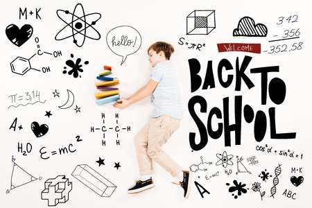 Top view of kid near colorful books and welcome back to school lettering on white background
