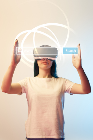 Young woman in vr headset holding search bar illustration on beige and blue background Stock Photo