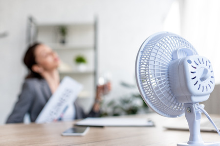 Selective focus of businesswoman suffering from heat while sitting near electric fan Stock Photo