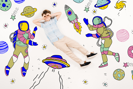 Cute kid with hands near eyes flying in space near astronauts on white background 스톡 콘텐츠