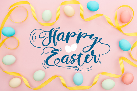 Top view of painted multicolored chicken eggs and satin yellow ribbon on pink background with happy Easter lettering Stock Photo