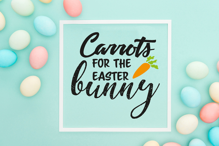 Top view of carrots for the Easter bunny lettering in white square frame near painted chicken eggs on blue background