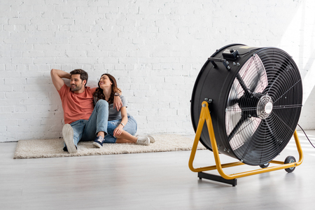 Young smiling couple sitting on floor by white wall background in front of blowing electric fan