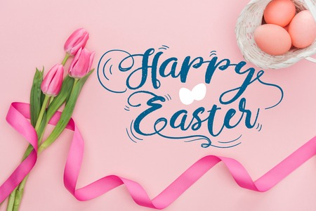 Top view of pink tulips bouquet with ribbon and painted eggs in wicker basket with happy Easter blue lettering on pink background