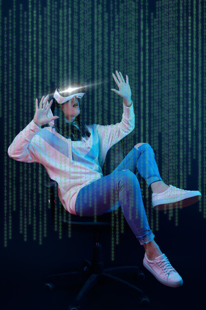 Young shocked woman in virtual reality headset sitting on chair and gesturing among data illustration on dark background