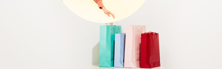 Panoramic shot of girl and colorful shopping bags on white background with yellow circle and copy space