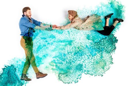 Elegant woman levitating in air and holding hands with man on background with watercolor turquoise spills