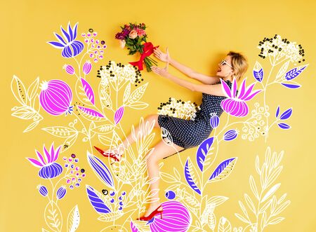 Top view of young happy elegant woman with bouquet of roses lying on yellow background with floral illustration Stock Photo