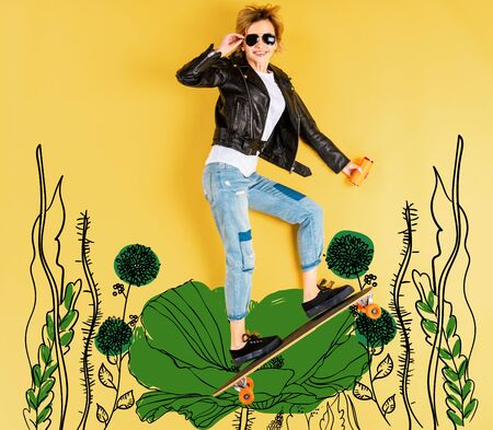 Top view of woman in leather jacket with longboard on yellow background with floral illustration Фото со стока