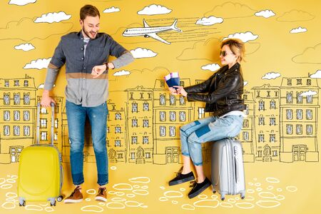 Happy woman holding passports and tickets while man with suitcase checking time with city and airplane illustration on yellow background Standard-Bild - 124465483
