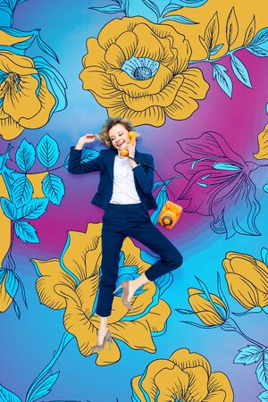 Top view of businesswoman in suit and high-heeled shoes talking on telephone while lying on blue background with flowers illustration