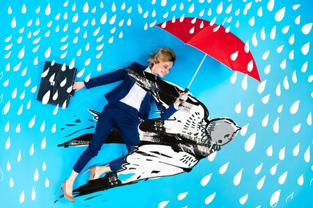 Top view of businesswoman in suit with umbrella and briefcase lying on blue background with swallow and rain illustration