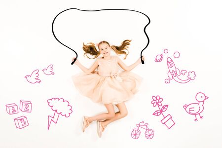 Top view of cheerful kid flying with jumping rope and smiling isolated on a white background