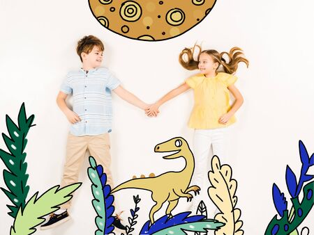 Top view of cheerful kids holding hands near dinosaur isolated on a white background 스톡 콘텐츠