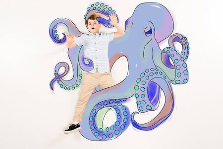 Top view of scared kid gesturing near blue octopus with tentacles isolated on a white background