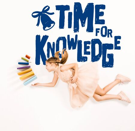 Top view of cheerful kid in pink dress holding books and flying near time for knowledge lettering isolated on a white background