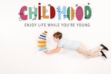 Top view of kid holding books and flying near childhood enjoy life while youre young lettering isolated on a white background
