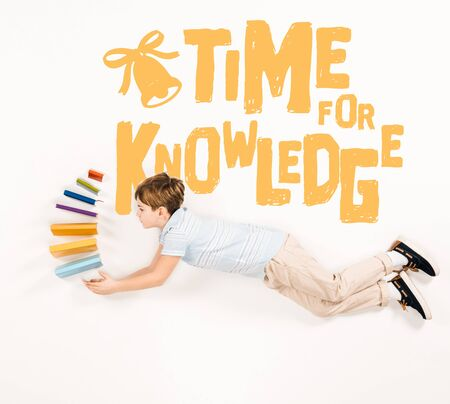 Top view of kid holding books and flying near time for knowledge lettering isolated on a white background