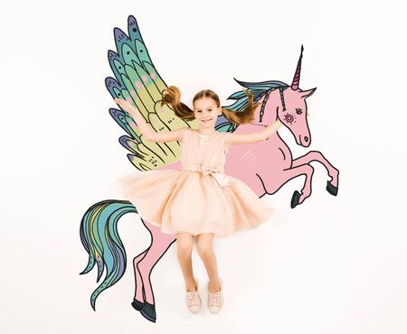 Top view of cheerful kid looking at camera and gesturing near unicorn isolated on a white background