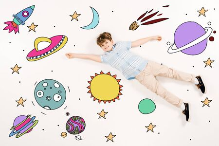 Top view of cheerful kid flying in space isolated on a white background