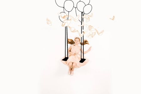 Top view of cheerful kid in pink dress on swing near birds and balloons isolated on a white background 스톡 콘텐츠