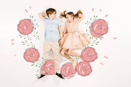 Top view of cheerful kids holding hands near pink flowers isolated on a white background 스톡 콘텐츠