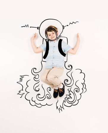 Top view of cheerful kid in astronaut suit gesturing isolated on a white background 스톡 콘텐츠