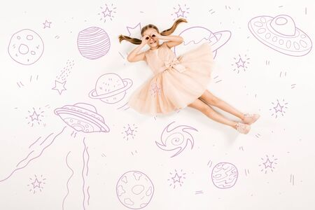 Top view of cheerful kid in pink dress with hands near eyes in space isolated on a white background 스톡 콘텐츠